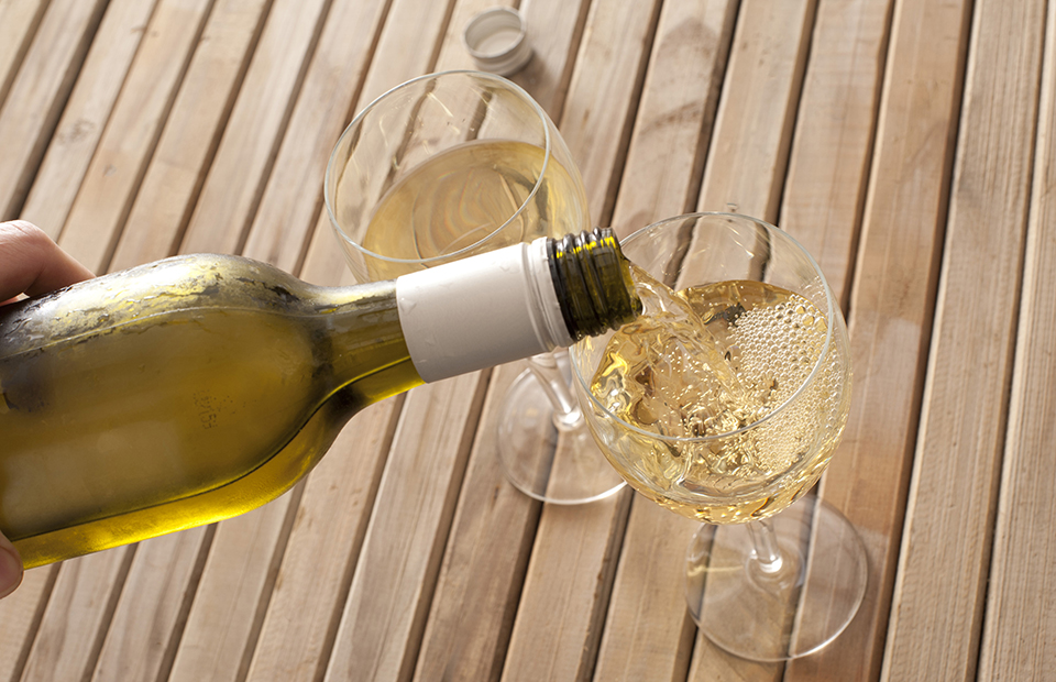 Pouring Glasses of Chilled White Wine